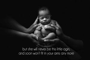 newborn photographer London: black and white image of baby inside mum and dad'd hands