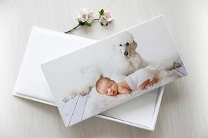 image of newborn with dog printed in a white leatherette album