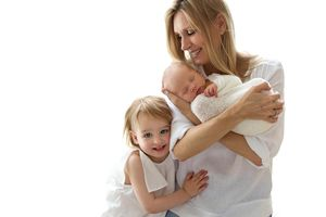 mum with her children: newborn in her arms and big sister hugging her