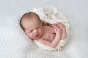 newborn baby sleeping on a white blanket
