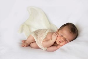 newborn sleeping with hands under his face on white blanket - london newborn photographer