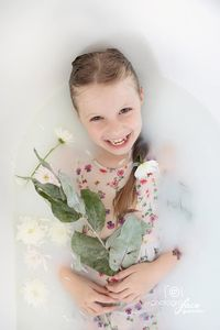 smiling girl in tub with flowers