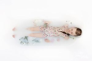 girl in white milk and flowers in a bathtub