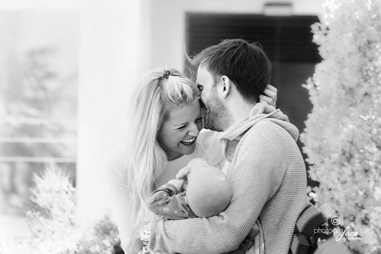 mum and dad hugging and laughing while holding baby - value of a photograph