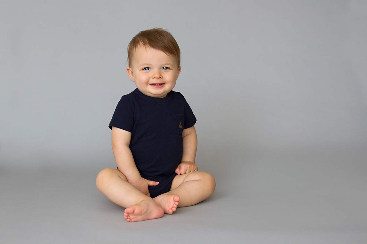 1 birthday photo - baby sitting on a grey background