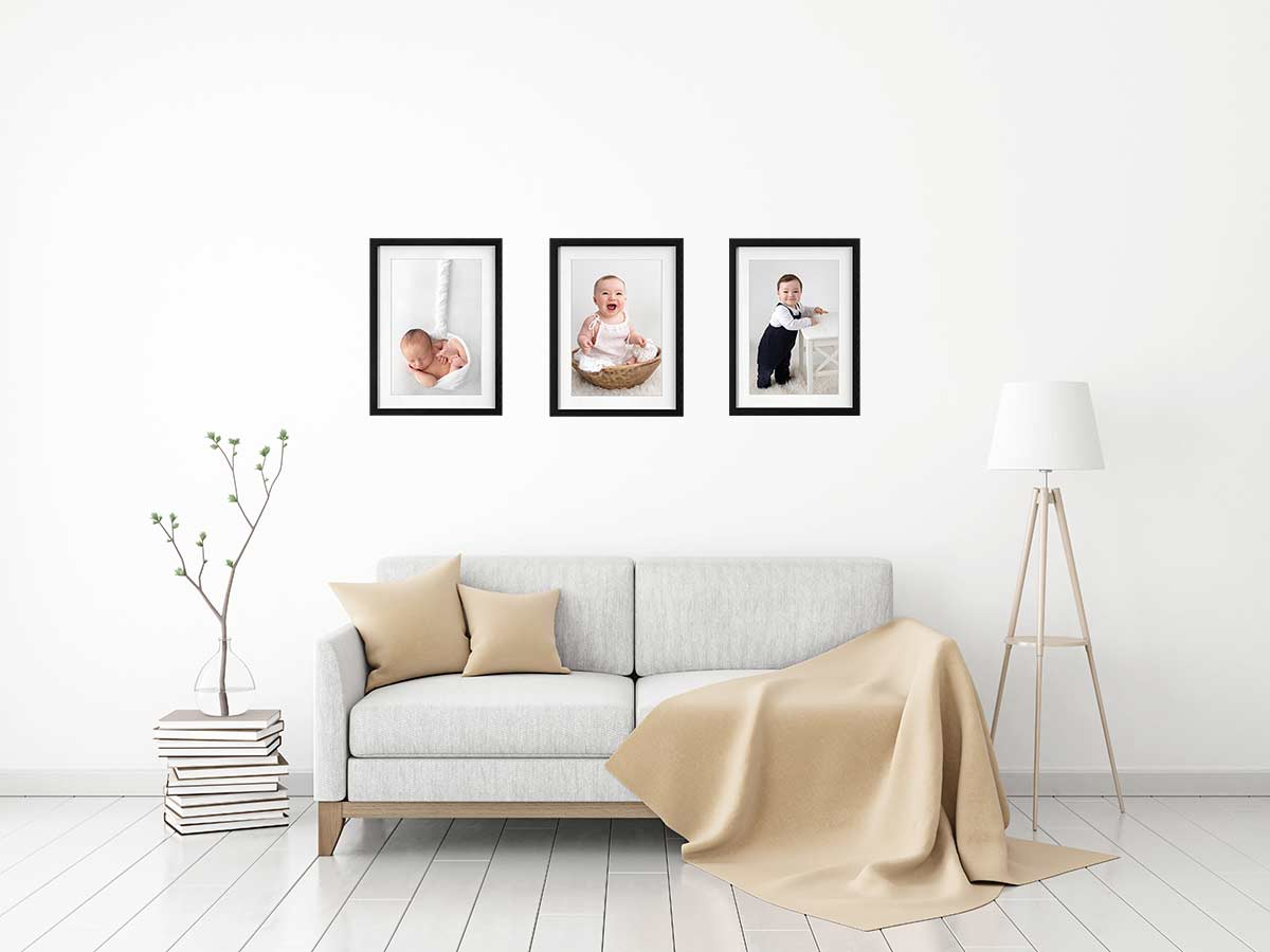 living room with 3 frames displaying baby and newborn photography
