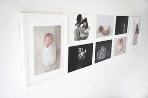 wall with portraits of newborn and babies in the studio of newborn photographer valentina in Richmond London