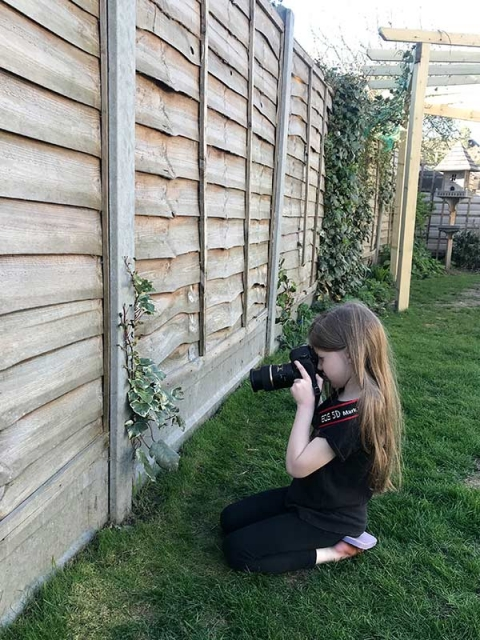 photography games for children: girl photographing an item from a photo scavenger hunt.