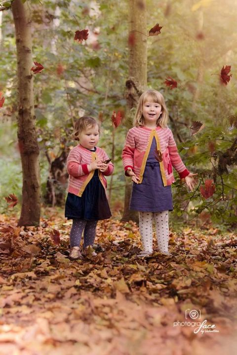 sisters in a park throwing autumn leaves