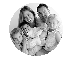 black and white family portrait: mum holding newborn baby and dad with the other 2 girls around her