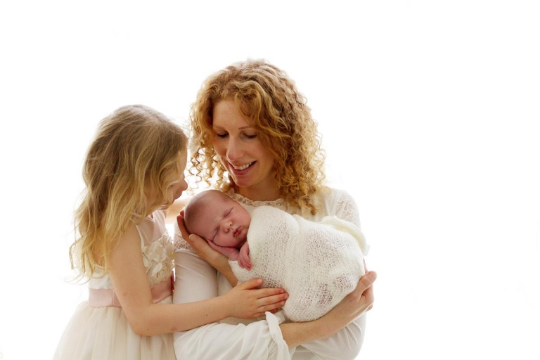 what to wear during a newborn session: mum with her girls dressed in white